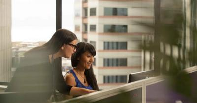 An image of two women at a desk