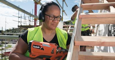 A picture of a  Pacific woman constructing a house